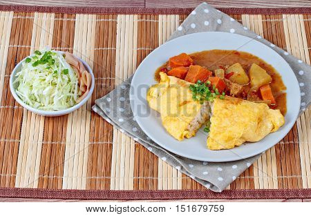 Omelet rice topped Japanese yellow curry  with sliced cabbage and pickled ginger are popular food for health.