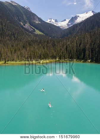 Stand up paddle boarders on a glacier fed lake in BC