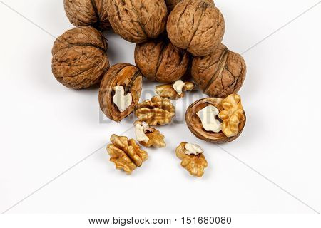 Whole walnuts and kernels on a table on a white background