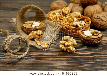 Whole walnuts and kernels on a table on sackcloth
