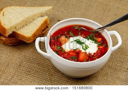 Traditional Ukrainian borsch with sour cream, meat, garlic and parsley
