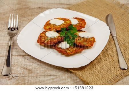 Potato pancakes with sour cream and parsley on a wooden table