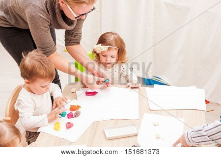 The teacher helps the girl to make a figure plasticine on the table