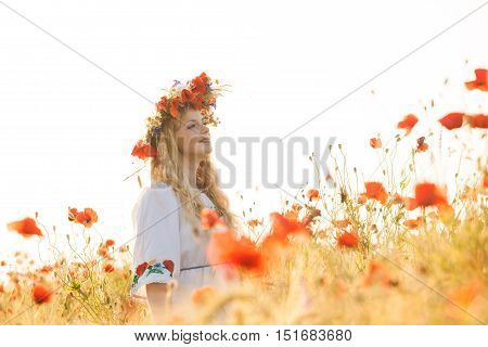 Pretty blonde girl in a dress with a pattern poppy and with a wreath on his head enjoying in a field with poppies