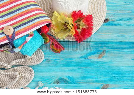 Beach bag, hat and other beach stuff on blue wooden background.