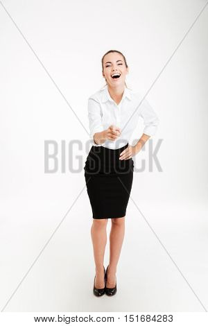 Young laughing beautiful businesswoman pointing at camera isolated on the white background