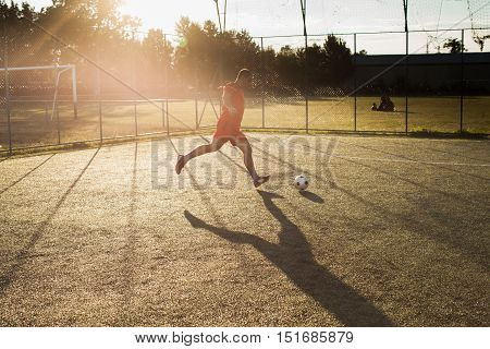 Football player in red. Man kicking ball in the grass outdoors