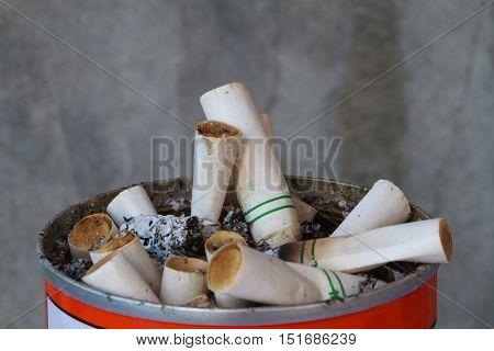 Cigarette butts discarded in sand basket on gray background.