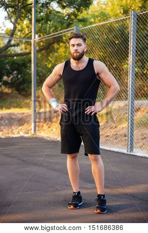 Concentrated young bearded man in sportswear standing with hands on hips outdoors