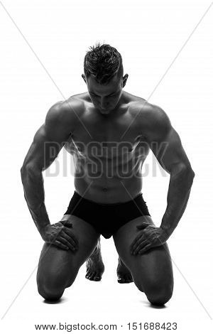 The beautiful and strong young guy.  Black and white photo, silhouette. Hidden in the shadow. Male silhouette. Sitting. Meditation. Getting ready for.