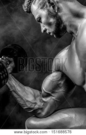 Closeup of a handsome power athletic man bodybuilder doing exercises with dumbbell. Fitness muscular body on dark smoky background. Selective Focus. Awesome bodybuilder, posing. Black and white.