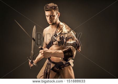 Portrait of angry gladiator with sword looking up against of black background. Isolated