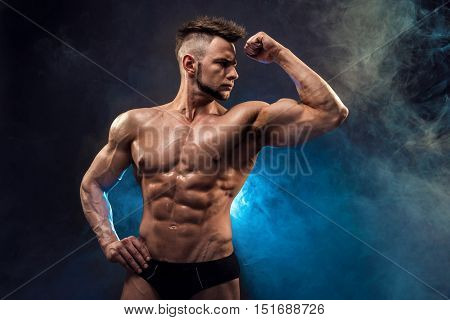 Handsome power athletic man bodybuilder. Wet Fitness muscular body on dark smoke background. Perfect male. Awesome bodybuilder, posing.