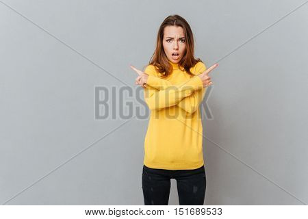 Portrait of a cheerful woman in yellow sweater pointing fingers away isolated on a gray background