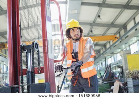 Young manual worker pushing hand truck in metal industry