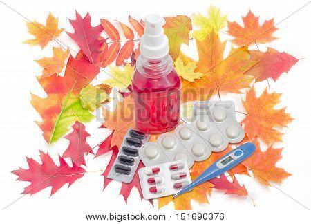 Blue electronic medical thermometer throat spray several packaging of medications and autumn leaves on a light background