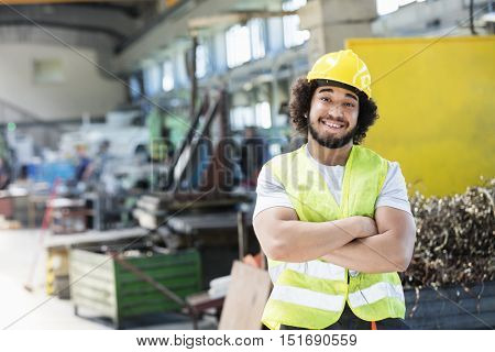Portrait of smiling male manual worker standing arms crossed in metal industry