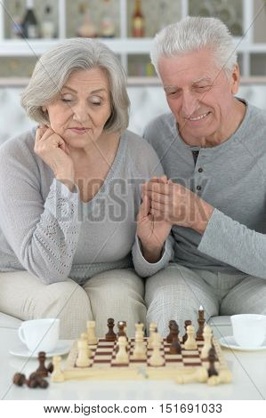 happy Senior couple resting at home and playing chess