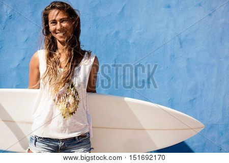 surfer girl with surfboard in front of blue wall