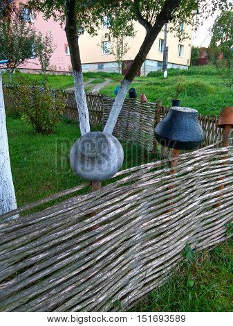 Ukrainian decoration wooden fence of twigs with pots and Kazan