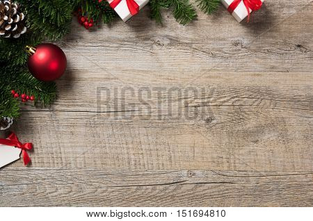 High angle view of christmas ornaments on wooden table with copyspace. Top view of xmas fir branch with white gift boxes and red ball. Rustic christmas corner background.