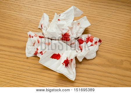 a bloody tissue on a wood table