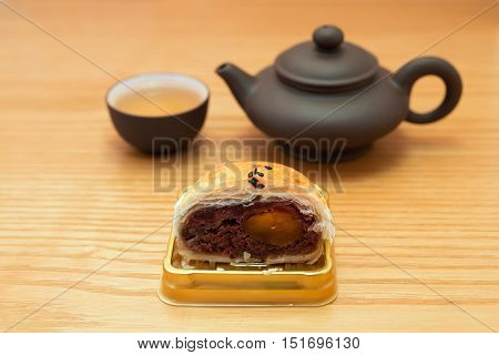 traditional chinese snack of preserved egg cakes cut out with tea on a wood table