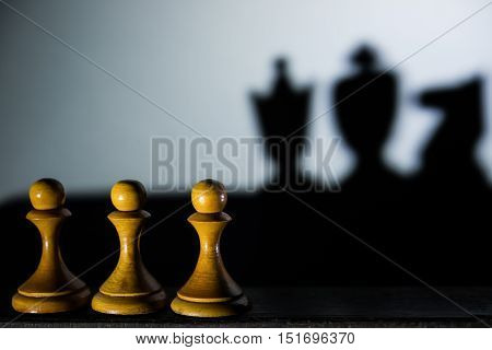 three chess pawn casting Queen King and Knight shadow in dark concept of strength and aspirations
