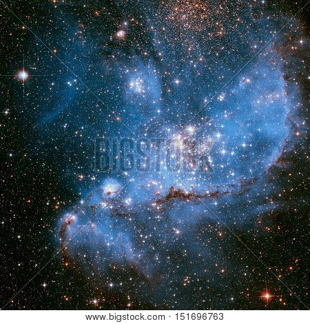 The Small Magellanic Cloud is a dwarf irregular galaxy near the Milky Way, located 210, 000 light-years away. Retouched colored image. Elements of this image furnished by NASA.
