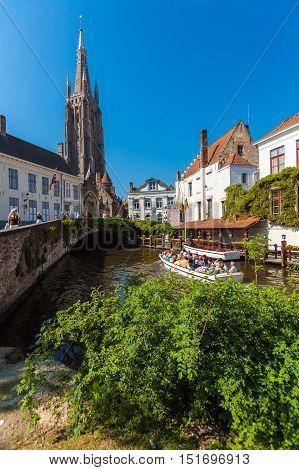 Bruges, Belgium - April 6, 2008: Tourists Float On A Boat L Near  Dijver Bridge