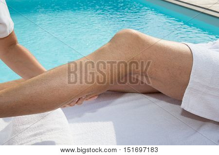 Osteopath Applying Pressure With Thumb On Male Calf Muscle.