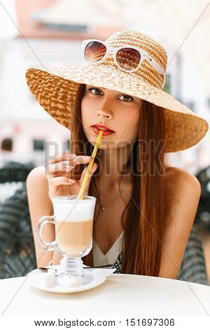 Beautiful Stylish Woman Drinks Coffee On The Beach On A Sunny Summer Day.