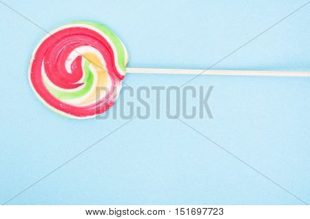 Closeup of swirl lollipop on blue background with text area