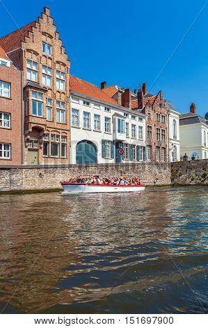 Bruges, Belgium - April 6, 2008: Tourists Float On A Boat Through The Dijver Channel