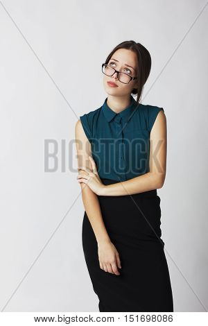 Young business woman in glasses, looks up wearily.