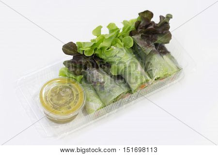 close up vegetable salad roll by rotee bandle with spicy seafood suace in plastic box package on white background