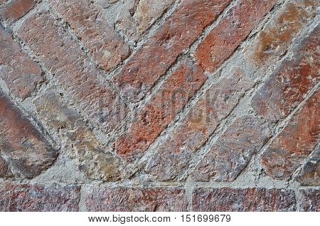 Fragment of old brick wall with herringbone pattern
