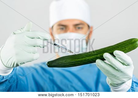 genetically modified food - scientist make injection in cucumber with syringe