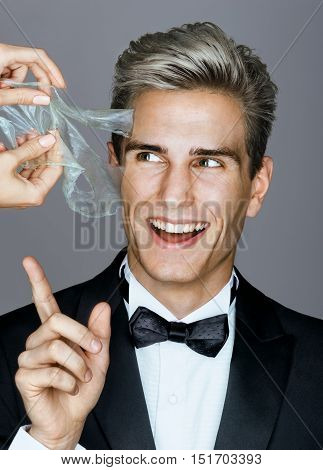 Smiling man in black suit removes peeling off a facial mask. Photo happy rich man on gray background. Skin care concept
