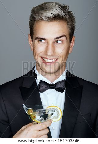 Time to flirt. Beautiful smiling handsome man in black suit with glass of martini. High life