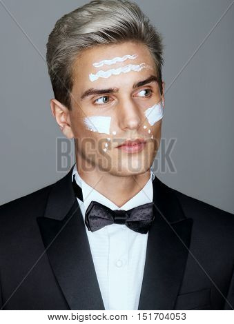 Beautiful face of imposing man with cosmetic cream on cheeks spa treatment. Portrait of man with healthy and perfect skin