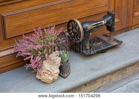 Soft focus pot of Erica carnea flower next to antique sewing machine decorating house and old styled iron in Florence, Italy