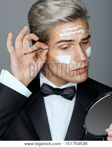 Intelligent and handsome man tweezing the hair on his face. Photo of gentleman looking in the mirror cares for his appearance. Grooming himself