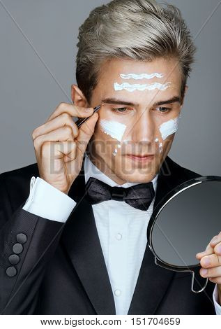 Getting ready for the ball. Photo of handsome man tweezing the hair on his face. Wrinkle cream or anti-aging skin care cream. Grooming himself