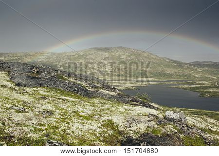 Dramatic landscape with beautiful rainbow over arctic meadows mountain and lake. Arctic summer the tundra Norway.
