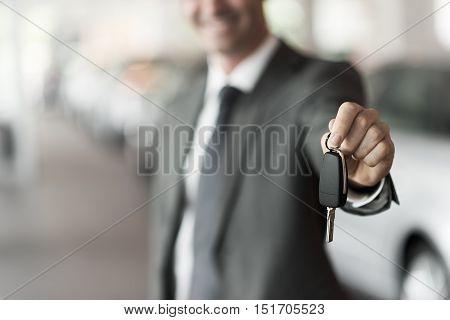 Smiling car salesman handing over your new car keys dealership and sales concept