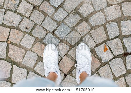 Young man traveling on summer vacation. White sneakers on tile.