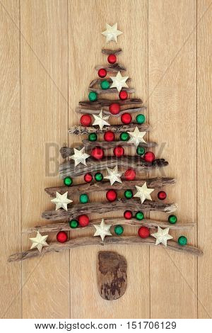 Driftwood christmas tree with red and green and star bauble decorations over oak wood background.