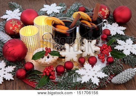 Christmas party food and drink with mulled wine, mince pie, snowflake gingerbread biscuits and baubles,  candles, red decorations, holly and snow covered fir.