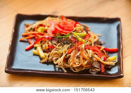 appetizing delicious fried noodles with vegetables on a black rectangular plate